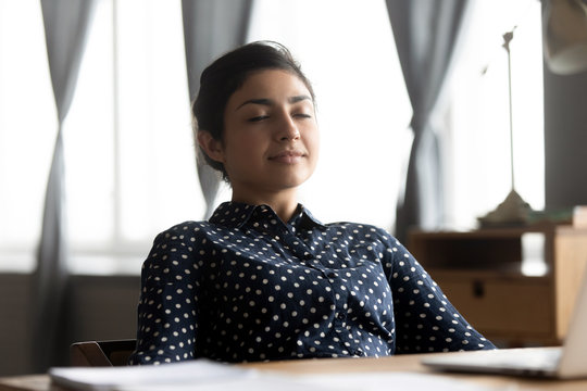 Relaxed indian young woman rest sit at desk eyes closed