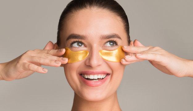 Pretty girl applying golden collagen patches under her eyes