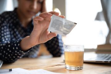 Ill woman pour medicine powder into glass relieve flu symptom