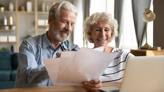 Senior couple use online banking on laptop planning family budget