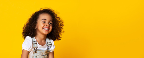 Cute little black girl sincerely laughing over yellow background, long panorama Fototapete