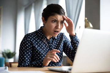 Shocked young indian girl look at laptop screen feel terrified