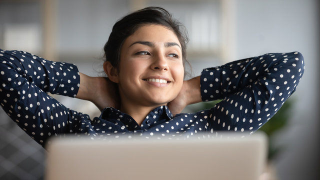 Happy satisfied indian woman relax with laptop looking away dreaming