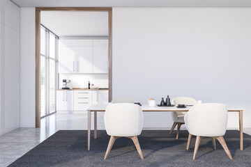 White dining room with armchairs and kitchen