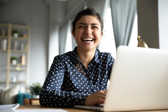 Cheerful indian girl laughing sit with laptop at table