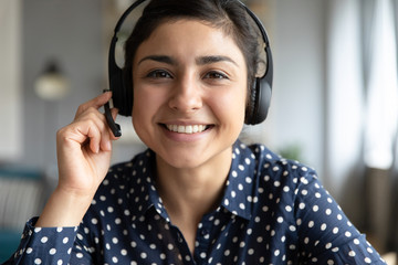 Smiling indian girl professional wear headset look at camera webcam