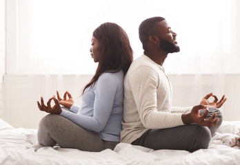 Expecting lady doing yoga with her husband at home