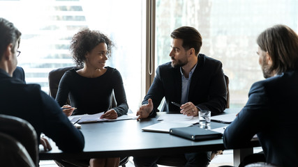 Multiracial businesspeople brainstorm discuss document at briefing