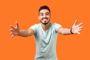 Come into my arms. Portrait of good natured, extremely happy brunette man with beard in white t-shirt reaching out to camera, stretching arms to hug you. studio shot isolated on orange background