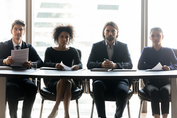 Portrait of multiracial businesspeople sit at desk in office