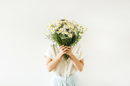 Young pretty woman with bouquet of white chamomile daisy flowers on white background.