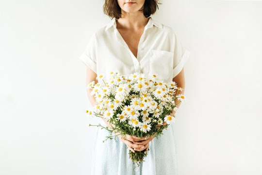 Young pretty woman hold in hands a bouquet of white chamomile daisy flowers on white background.