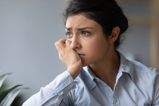 Sad melancholic indian woman looking away thinking of problems alone