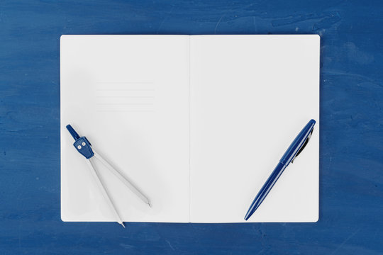 Classic blue colored top view photo of scattered stationery.