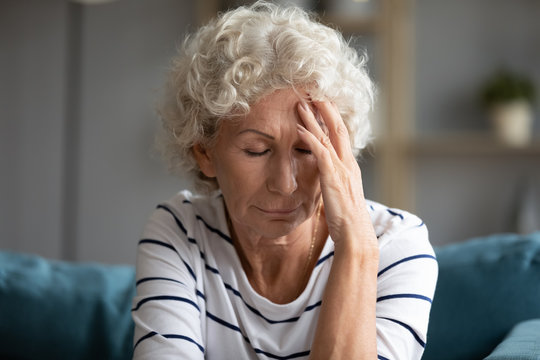 60s woman closed eyes touch forehead suffers from migraine