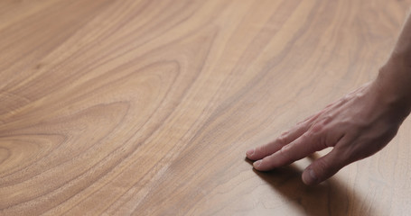 Photo sur Toile Les Textures man hand touches black walnut dining table surface