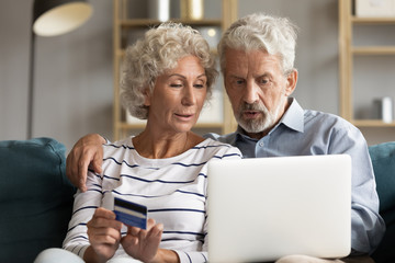 Senior couple use online websites bank credit card buying online
