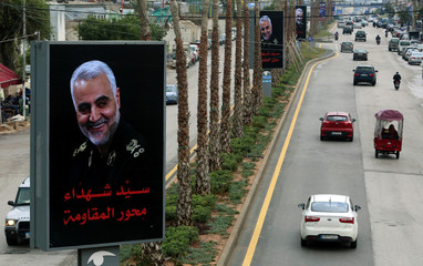 Cars pass near a picture of late Iranian Major-General Qassem Soleimani, head of the elite Quds Force, in Beirut's suburbs