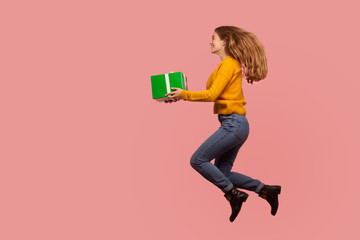 Full length portrait of cheerful excited ginger girl in sweater and denim jumping in air or flying...