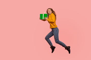 Portrait of extremely happy ginger girl in sweater and denim jumping in air with gift box, full of...
