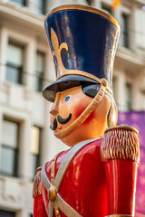 A life sized statue of a Christmas toy soldier with a red coat and blue hat stands guard in a city street mall in Melbourne, Australia.