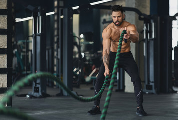 Wall Mural - Athletic young man with battle rope doing exercise