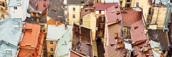 Photo sur Aluminium Marron chocolat View of the old roofs. Bright color roofs of houses in historical city center. Banner crop 3 in 1.