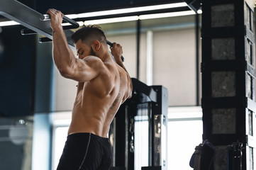 Wall Mural - Muscular athlete pulling up on horizontal bar at gym