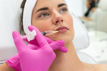 Fototapeta Modelowanie ust kwasem hialuronowym. Twarz kobiety, zabieg powiększania ust. Lekarz medycyny estetycznej wstrzykuje wypełniacz w usta.   obraz