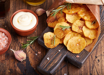 Crispy potato chips. Slices of potato, roasted with sea salt and rosemary. Delicious snack served with sauce. Fast food.