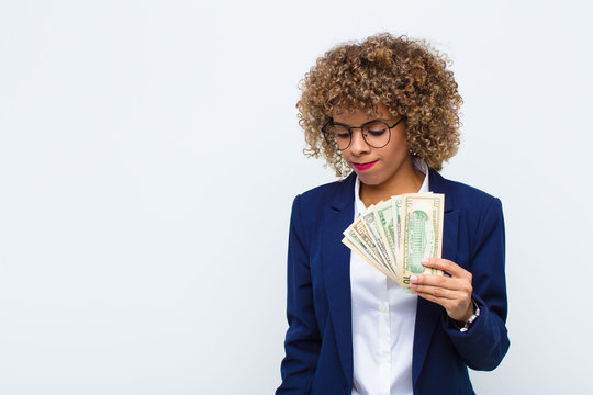 young african american woman feeling sad, upset or angry and looking to the side with a negative attitude, frowning in disagreement with euro banknotes