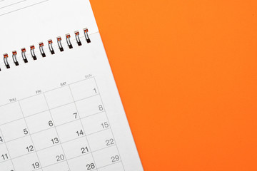 close up of calendar on the orange table, planning for business meeting or travel planning concept
