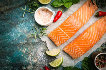 Raw salmon fillet and ingredients for cooking, seasonings and herbs on a blue background . Top view