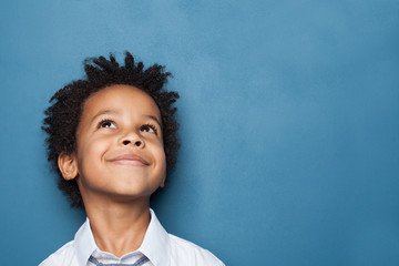 Little black child boy smiling and looking up on blue background Fototapete