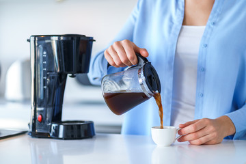 Woman using coffee maker for making and brewing coffee at home. Coffee blender and household kitchen appliances for makes hot drinks