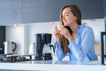 Happy attractive female enjoying of fresh coffee aroma after brewing coffee using coffee maker in the kitchen at home. Coffee blender and household kitchen appliances for makes hot drinks Fototapete