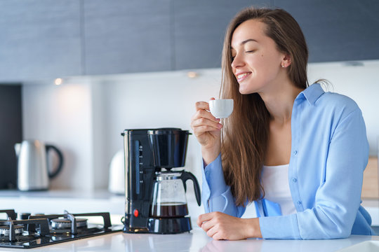 Happy attractive woman enjoying of fresh coffee aroma after brewing coffee using coffee maker in the kitchen at home. Coffee blender and household kitchen appliances for makes hot drinks