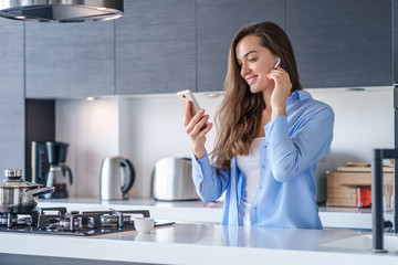 Young happy woman using smartphone and white wireless earphones for listening music and audio book in the kitchen at home. Modern mobile people Papier Peint
