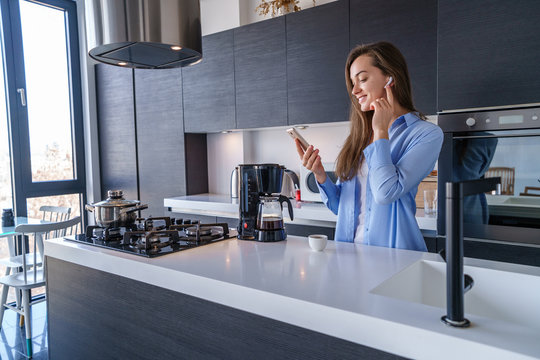 Young happy joyful female listening music using white wireless earphones and smartphone in the kitchen at home. Mobile people