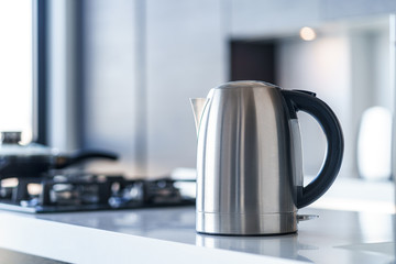 Silver metal electric kettle for boiling water and making tea on a table in the kitchen interior. Household kitchen appliances for makes hot drinks Fototapete