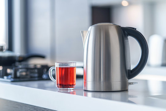 Electric kettle for boiling water and making tea on a table in the kitchen interior. Household kitchen appliances for makes hot drinks
