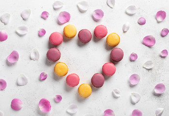 Valentine's Day heart made of assorted macarons different colors. white concrete background, top view