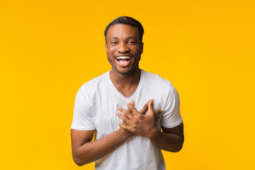 African American Man Laughing Touching Chest Standing Over Yellow Background