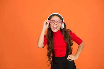 Spoed Foto op Canvas Muziekwinkel Cool track. Girl with eyeglasses orange background. Event and entertainment. Party girl. Party accessory. Having fun. Play list for party. Music concept. Kid wear eyeglasses. Eyewear fashion store