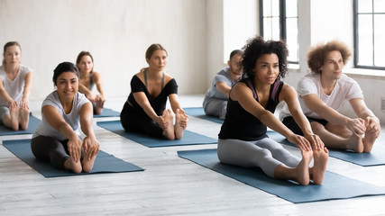 Diverse people with instructor doing Seated forward bend, practicing yoga