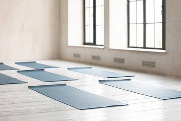Acrylic Prints Asia Country Unrolled yoga mats on wooden floor in empty fitness center