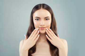 Pretty model woman smiling on light blue background. Clear skin, perfect manicure