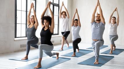 Photo sur Toile Ecole de Yoga Diverse people doing Warrior one exercise at group yoga lesson