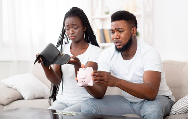 Unhappy afro couple shaking piggybank and wallet at home, searching money