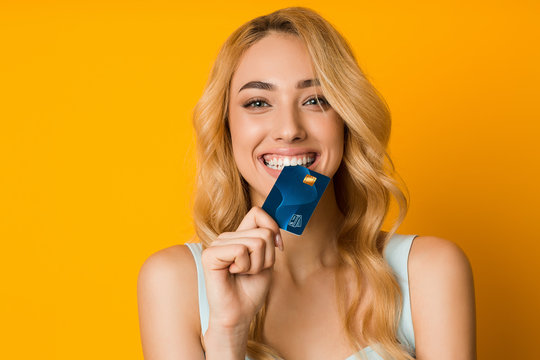 Playful girl biting credit card, thinking of doing online shopping